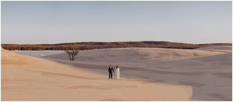 desert inspired elopement couple standing between sand dunes