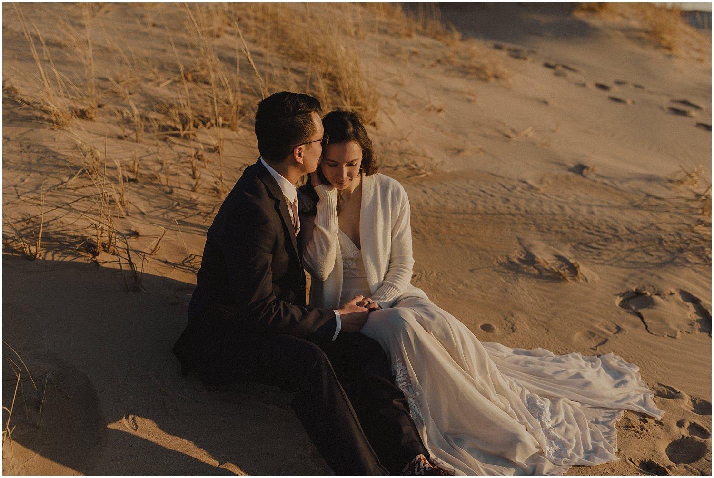 desert inspired elopement couple sitting on sand