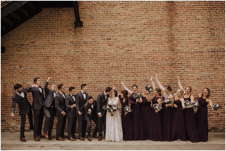 bridal party cheering as couple kiss