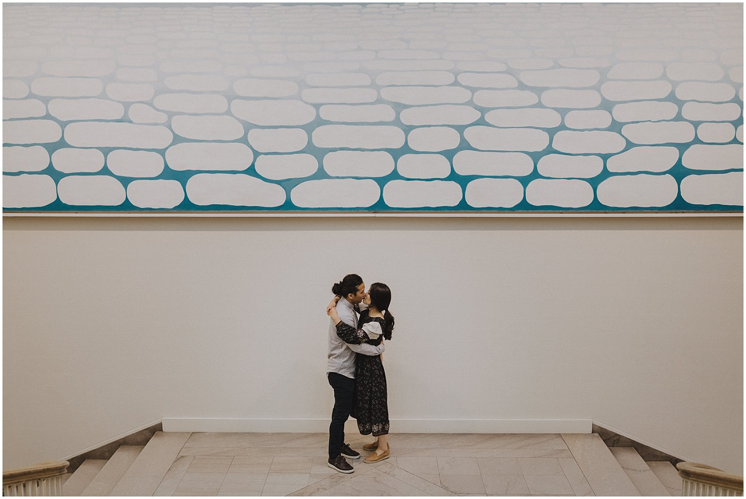 Couple kissing in front of art