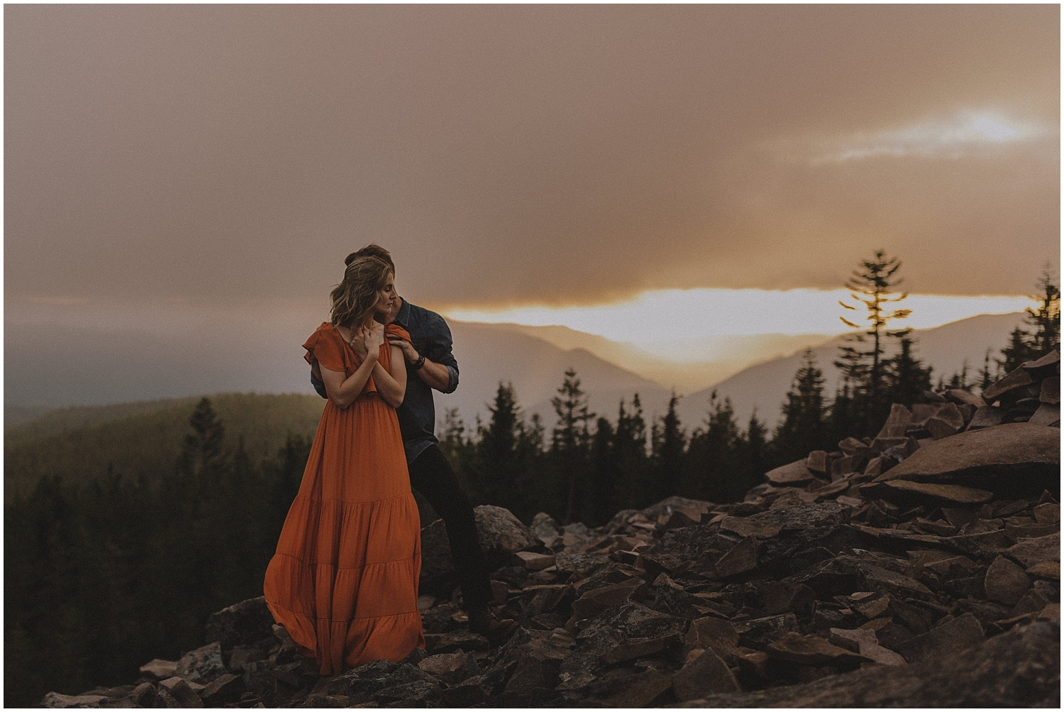 a couple standing on a mountain as the sun set behind them