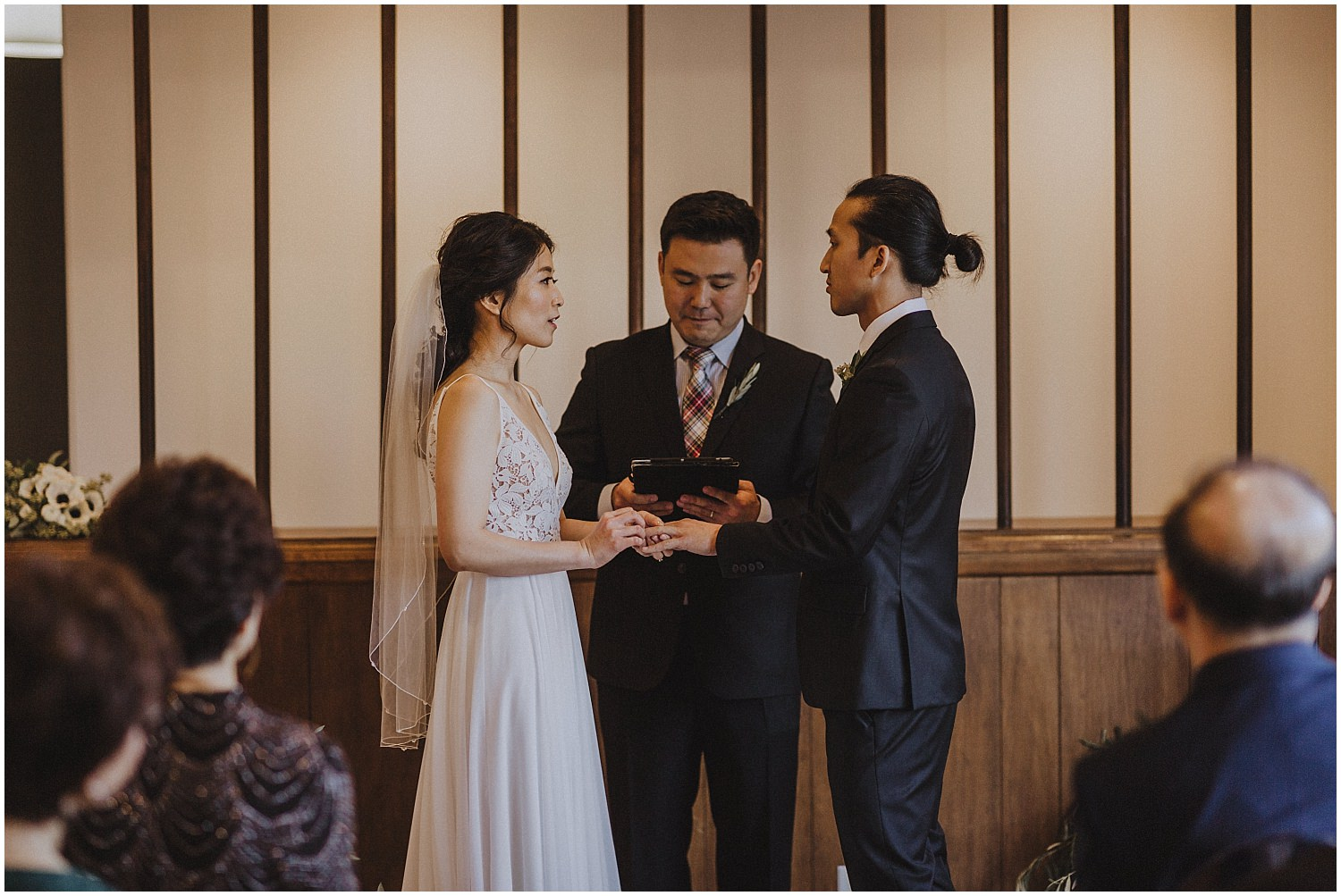 exchange of wedding rings at an in home wedding Chicago wedding photographer kyle szeto