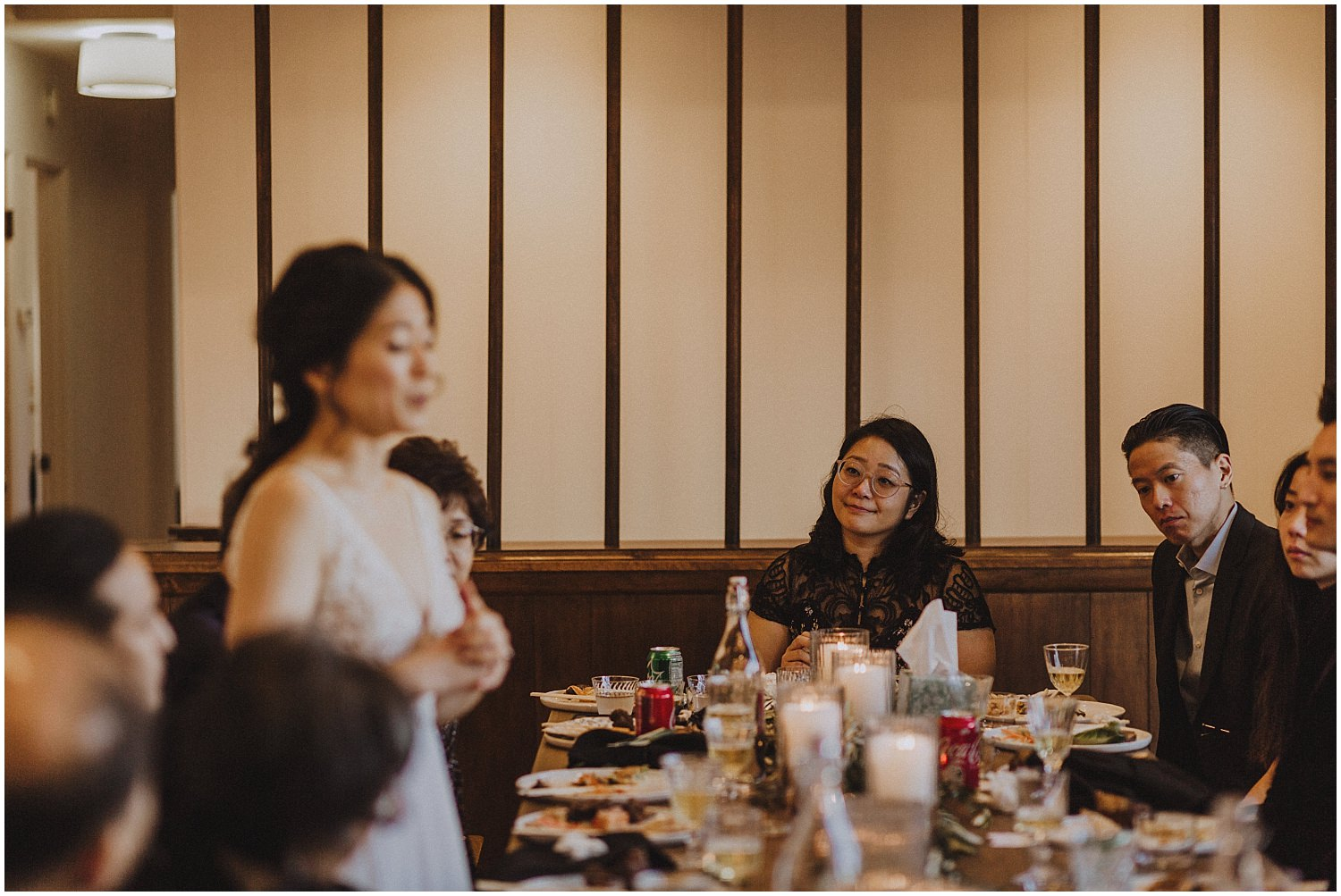 people looking on as a bride stands up and gives a speech Chicago wedding photographer kyle szeto