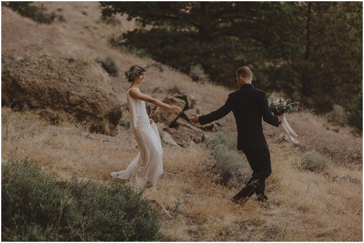 bride and groom walking down a mountain