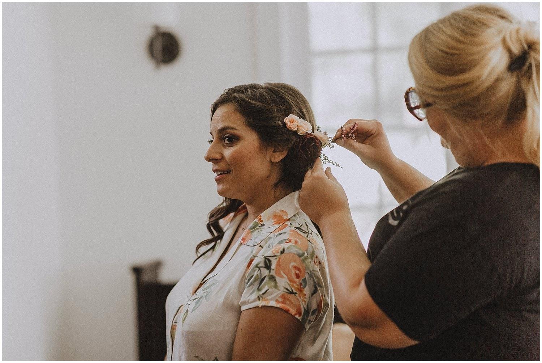 bride getting flowers in her hair wisconsin wedding elopement photographer kyle szeto