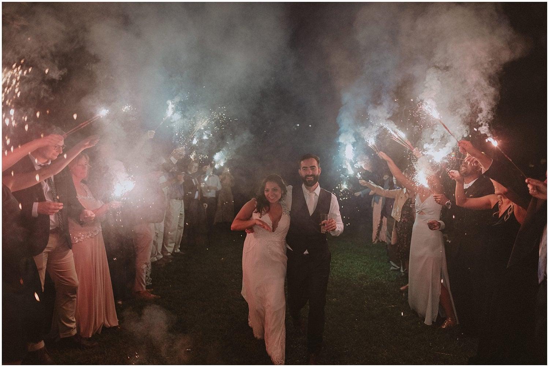 couple walking through flares and smoke guests dancing camp wandawega wedding reception wisconsin wedding elopement photographer kyle szeto